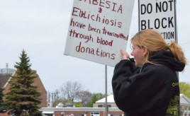 Protester, Lisa HIlton holds sign about Babesia being transmitted through the blood supply at 2013 Greenbay, Wi Worldwide Lyme Protest